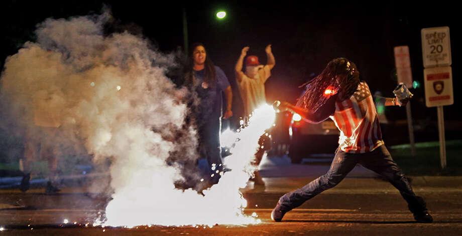This August 13, 2014, photo by St. Louis Post Dispatch photographer Robert Cohen shows Edward Crawford returning a tear gas canister fired by police who were trying to disperse protesters in Ferguson, Missouri.  Four days earlier, unarmed black teenager Michael Brown was shot to death by white police officer Darren Wilson. The killing ignited riots and unrest in the St. Louis area and across the nation. Cohen and members of the St. Louis Post Dispatch photo staff are winners of the 2015 Pulitzer Prize for Breaking News Photography it was announced Monday, April 20, 2015, at Columbia University in New York. (Robert Cohen, St. Louis Post Dispatch, Columbia University via AP) ORG XMIT: NYR204 / Columbia University
