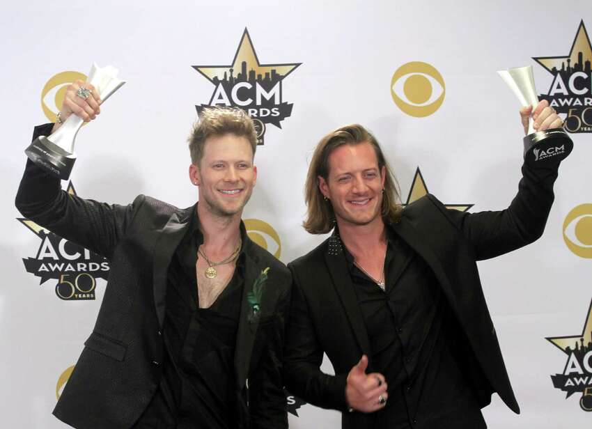 Brian Kelley, left, and Tyler Hubbard, of Florida Georgia Line, pose in the press room with the awards for vocal event of the year for