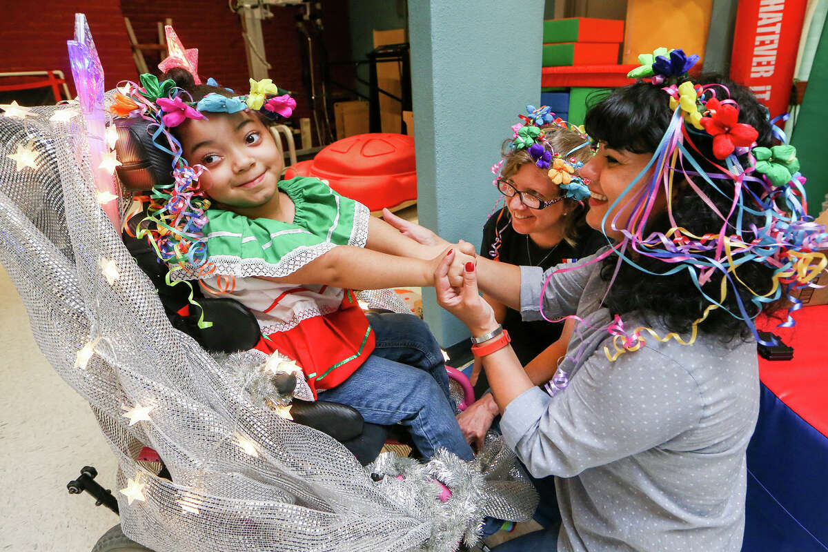 Cati Andreason (right) and Beth McMahon help decorate six-year-old Maliah Salas-Cook's wheelchair at TEAMability, 1711 N. Trinity, in preparation for the Texas Cavaliers River Parade on Monday, April 20, 2015. Salas-Cook and four others from the organization will ride in the parade as charitable honorees. MARVIN PFEIFFER/ mpfeiffer@express-news.net