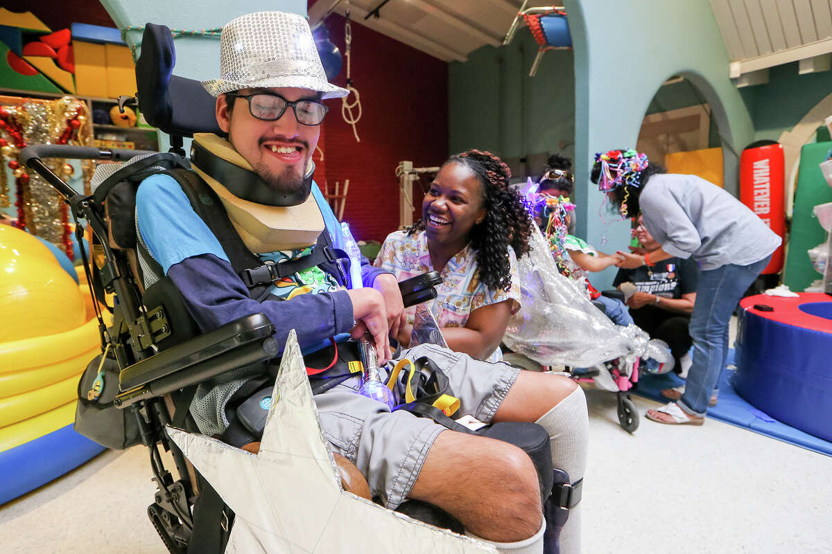 Lashanda Robinson decorates 17-year-old David Carrigan's wheelchair at TEAMability, 1711 N. Trinity, in preparation for the Texas Cavaliers River Parade on Monday, April 20, 2015. Carrigan and four others from the organization will ride in the parade as charitable honorees. MARVIN PFEIFFER/ mpfeiffer@express-news.net