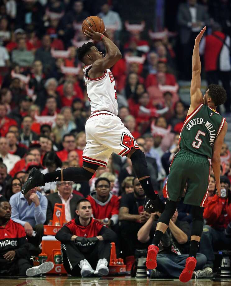 Jimmy Butler of the Bulls takes a running shot over Michael Carter-Williams of the Bucks on his way to 31 points in Chicago's second consecutive home playoff victory. Photo: Jonathan Daniel, Getty Images