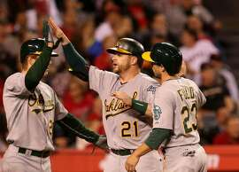 ANAHEIM, CA - APRIL 20:  Stephen Vogt #21 of the Oakland Athletics is greeted by Sam Fuld #23 and Mark Canha #20 after all three score on Vogt's three run home run in the third inning against the Los Angeles Angels of Anaheim at Angel Stadium of Anaheim on April 20, 2015 in Anaheim, California.  (Photo by Stephen Dunn/Getty Images)