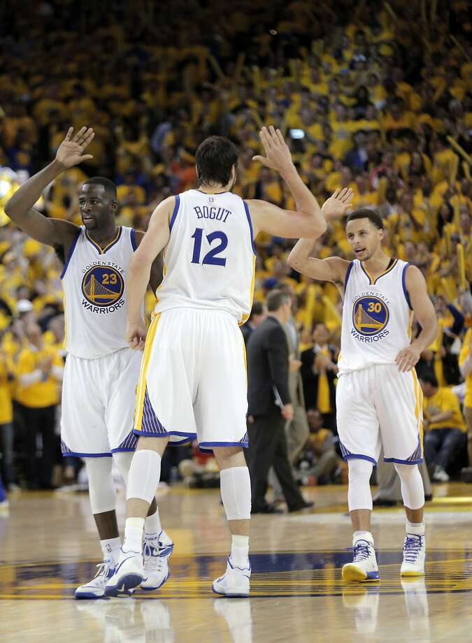 Warriors Draymond Green (23), Andrew Bogut (12) and Stephen Curry (30) celebrate during a timeout during the second half. The Golden State Warriors played the New Orleans Pelicans in Game 2 of the 1st Round of NBA Western Conference Playoffs at Oracle Arena in Oakland, Calif., on Monday, April 20, 2015. Photo: Carlos Avila Gonzalez, The Chronicle