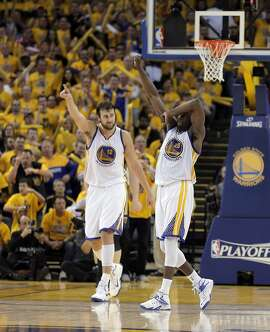 Andrew Bogut (12) and Draymond Green (23) gesture after the Pelicans were called for traveling during the second half. The Golden State Warriors played the New Orleans Pelicans in Game 2 of the 1st Round of NBA Western Conference Playoffs at Oracle Arena in Oakland, Calif., on Monday, April 20, 2015.