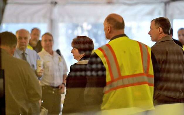 Albany Mayor Kathy Sheehan, center, listens during a Tuesday morning briefing about the mudslide that blocked the Normans Kill between Albany's Capital Hills Golf Course and Normanside Country Club in Bethlehem. (Skip Dickstein / Times Union)