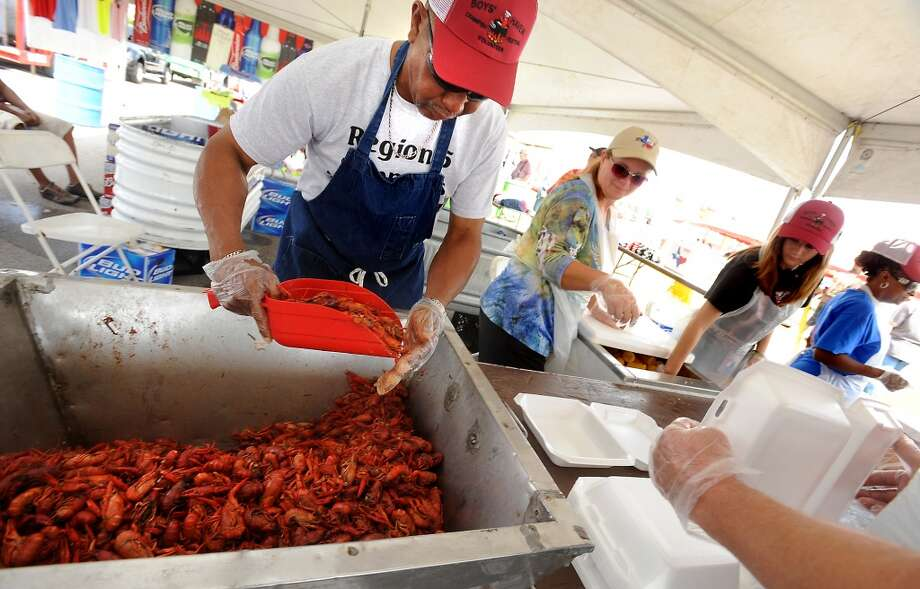 Roy Lightfoot dishes out a scoopfull of crawfish during the Boys' Haven Crawfish Food and Music Festival at the Parkdale Mall in Beaumont, Saturday. Tammy McKinley/The Enterprise