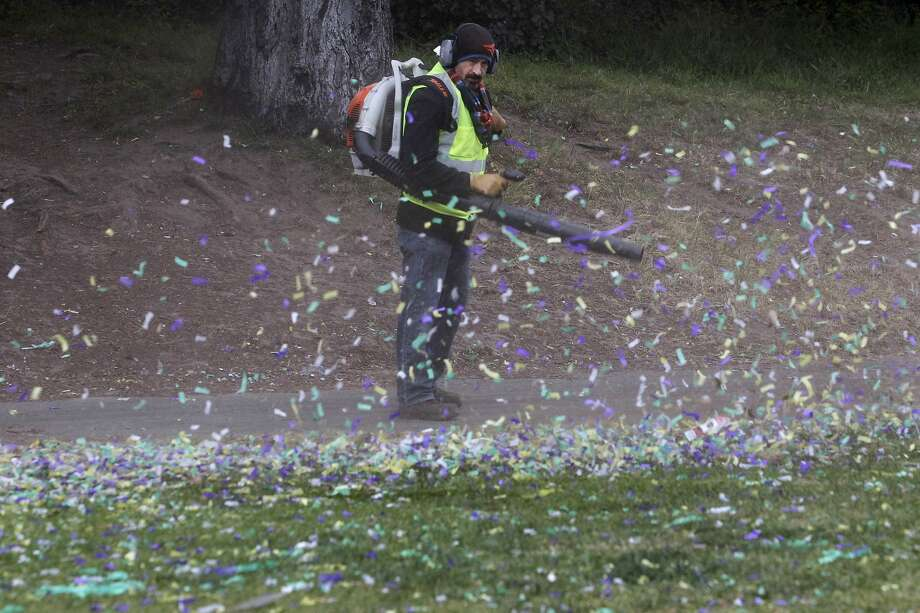 Juan Velez from the Recreation and Parks Department moves confetti to one side of the lawn as the clean-up continues on Hippie Hill and Sharon Meadow at Golden Gate Park in San Francisco, Calif. on Tuesday, April 21, 2015, after yesterday's smoke-out to mark the 4/20 marijuana celebration. Crews picked up the bulk of the trash Monday evening after the large crowd had finally dispersed. Photo: Paul Chinn, The Chronicle