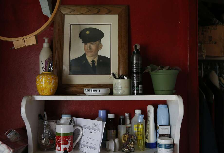 An old military portrait of the late Wayne Stafford, the husband of Dorie Stafford in Dorie's room in the home of friends Sue McPheeters and Joe Eddleman where she is staying Feb. 7, 2015 in Ukiah, Calif. Stafford, who is on Social Security, moved in with her longtime friends over a year ago because she couldn't afford a place of her own. The home does not have electricity, and though Stafford respects the lifestyle her friends choose to have, she says she wishes she could have her own place and electricity. Her husband Wayne died in 2007 in a motorcycle accident, three years after filing a disability claim with the Oakland VA for the time he spent serving in the Korean War which involved exposure to Agent Orange. Wayne never received a response from the VA while he was alive. Photo: Leah Millis, The Chronicle