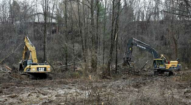 Excavators work in concert at the Capital Hill at Albany Golf Course Tuesday morning April 21, 2015 to make repairs at the mudslide site on the Normans Kill that borders Albany and Bethlehem, N.Y.       (Skip Dickstein/Times Union) Photo: SKIP DICKSTEIN / 00031544A