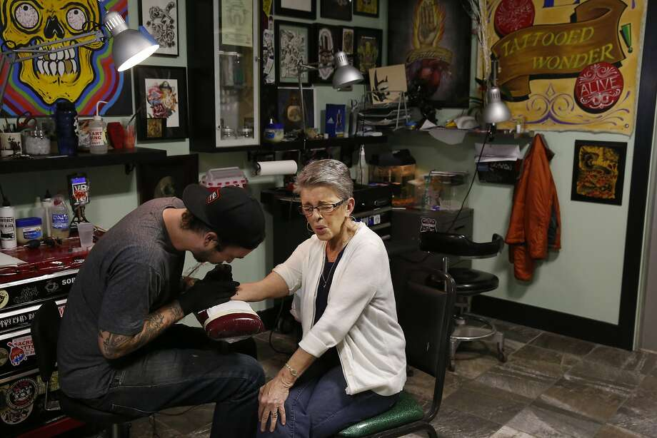 Rustyann Brown reacts to Seth Singletary as he draws her tattoo showing the number of compensation claims she found in a cabinet when she worked at the VA at Sacred Tattoo March 31, 2015 in Oakland, Calif. Brown became a whistleblower last year while working for the Oakland VA after she discovered over 13,000 compensation and disability claims stashed away in a filing cabinet dating back to the early 90s. Since she reported the VA, she says not much has changed within the office. Brown left the VA not long after coming forward with the news and has since been plagued with guilt and concern over the claims. Photo: Leah Millis, The Chronicle