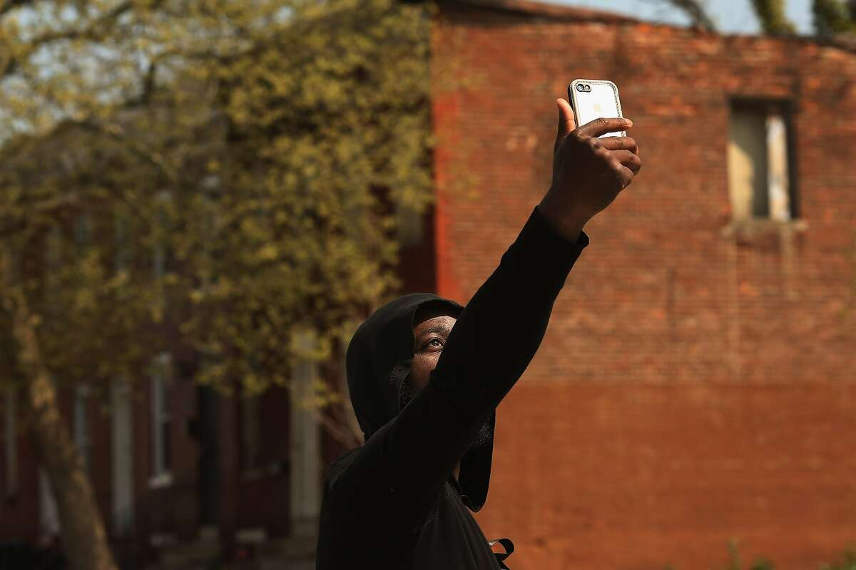 BALTIMORE, MD - APRIL 21: A young man who game his name only as Raheem video chats with a friend near the place where Freddie Gray was arrested in the Sandtown neighborhood April 21, 2015 in Baltimore, Maryland. Gray, whose nickname was Pepper, was a 25-year-old black man who lived in this neighborhood and was arrested for possessing a switch blade knife April 12 outside the Gilmor Homes housing project on Baltimore's west side. According to his attorney, Gray died a week later in the hospital from a severe spinal cord injury he received while in police custody. (Photo by Chip Somodevilla/Getty Images)