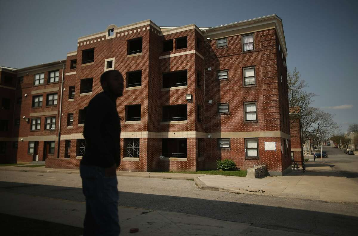 BALTIMORE, MD - APRIL 21: A young man stands outside the Gilmor Homes housing project building where Freddie Gray was arrested in the Sandtown neighborhood April 21, 2015 in Baltimore, Maryland. Gray, a 25-year-old black man who lived in the neighborhood, was arrested for possessing a switch blade knife April 12 outside this building on Baltimore's west side. According to his attorney, Gray died a week later in the hospital from a severe spinal cord injury he received while in police custody. (Photo by Chip Somodevilla/Getty Images)