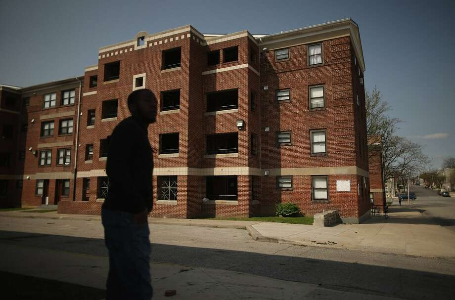BALTIMORE, MD - APRIL 21:  A young man stands outside the Gilmor Homes housing project building where Freddie Gray was arrested in the Sandtown neighborhood April 21, 2015 in Baltimore, Maryland. Gray, a 25-year-old black man who lived in the neighborhood, was arrested for possessing a switch blade knife April 12 outside this building on Baltimore's west side. According to his attorney, Gray died a week later in the hospital from a severe spinal cord injury he received while in police custody.  (Photo by Chip Somodevilla/Getty Images) Photo: Chip Somodevilla, Getty Images