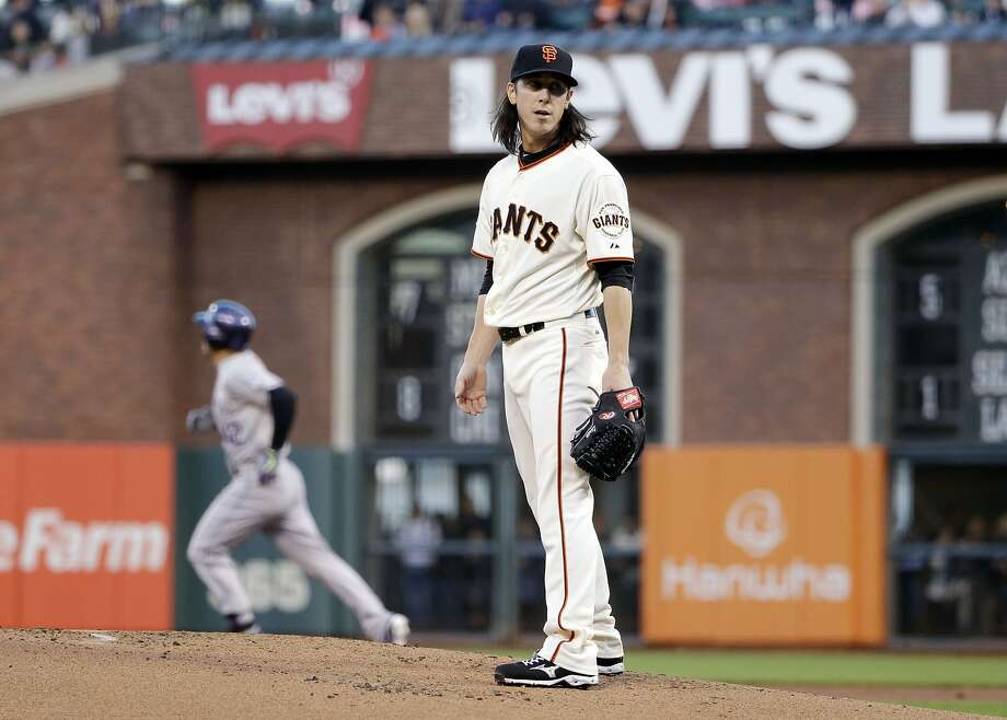 Colorado Rockies' Nolan Arenado, left, rounds the bases after his three-run home run off San Francisco Giants starting pitcher Tim Lincecum, right, during the first inning of a baseball game on Wednesday, April 15, 2015, in San Francisco. (AP Photo/Marcio Jose Sanchez) Photo: Marcio Jose Sanchez, Associated Press