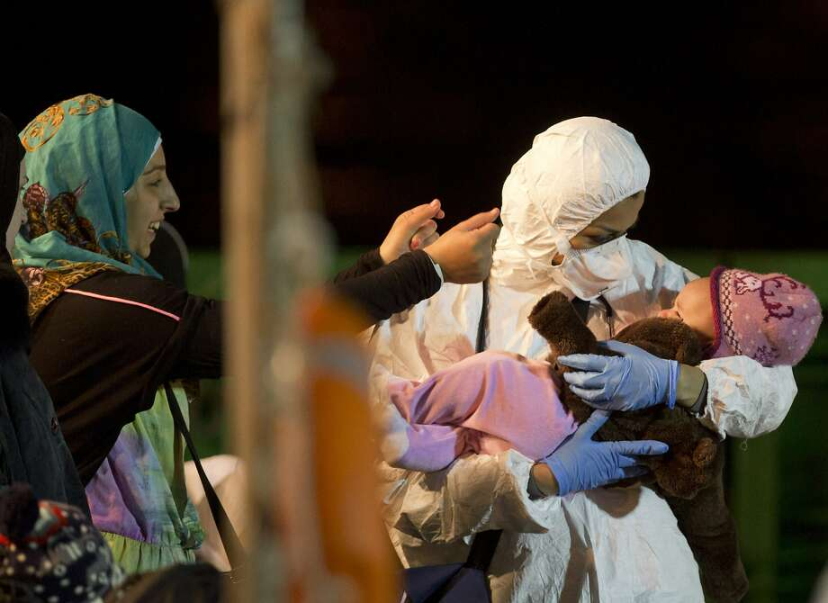 Rescuers cradle a child Monday in Pozzallo, Sicily. Italian ships have rescued 10,000 people in two weeks. Photo: Alessandra Tarantino, Associated Press