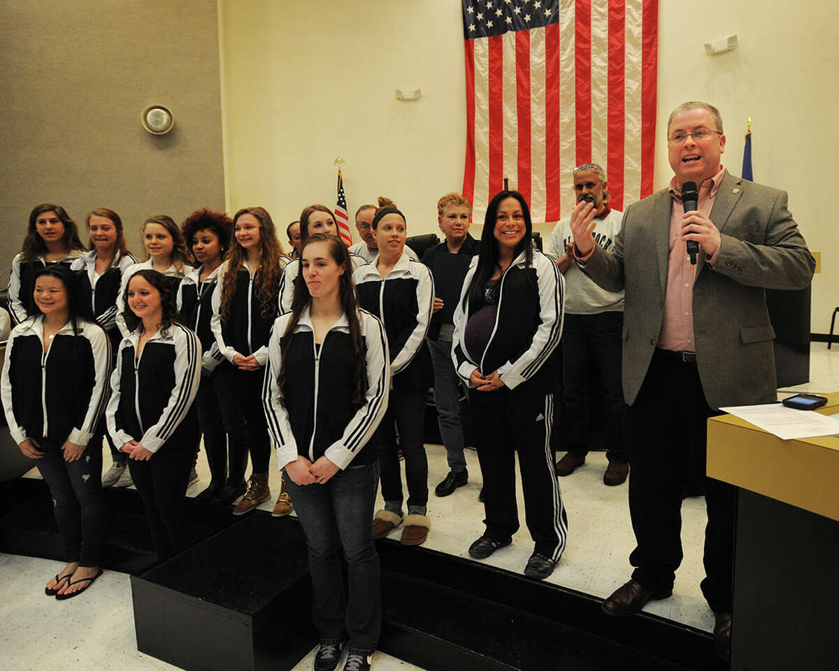 Standing in for an absent Mayor Bill Finch, Bridgeport City Council President Thomas McCarthy honors the University of Bridgeport's gymnastics team for their second place finish nationally at City Hall in Bridgeport, Conn. on Monday, April 20, 2015.