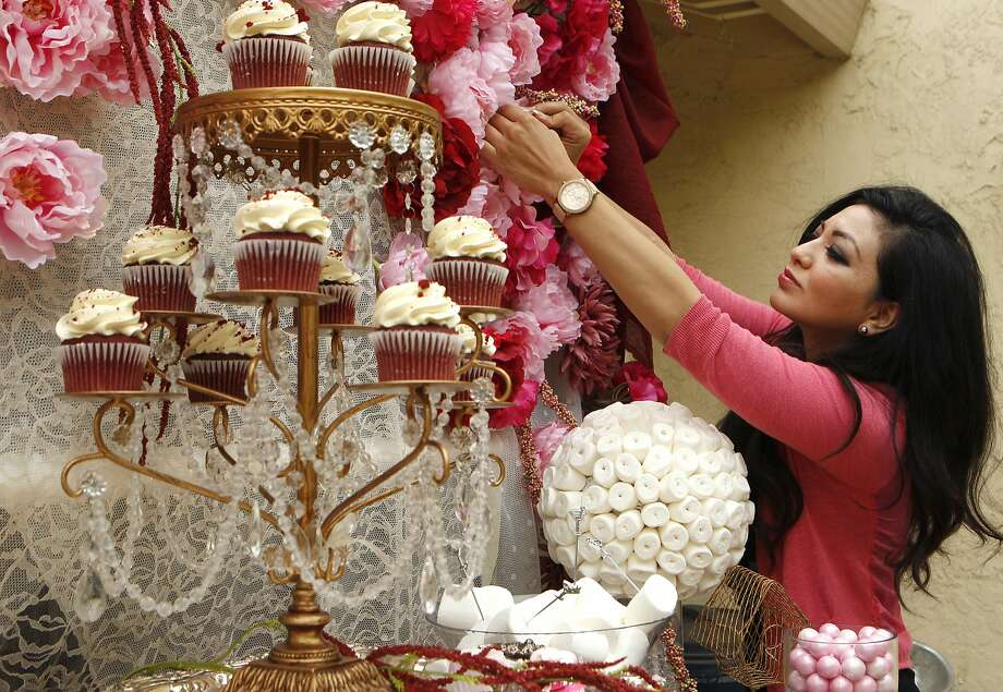 "Geraldine Orozco, founder and creative director of Bay Area Candy Buffet, arranges flowers during a ""dress rehearsal"" to prepare to cater for a client's wedding on Wednesday, pictured Tuesday, April 21, 2015, at her home in Union City, Calif. Bay Area Candy Buffet caters sweets to clients. Orozco uses Thumbtack.com, which connects consumers to home professionals. Photo: Santiago Mejia, The Chronicle"