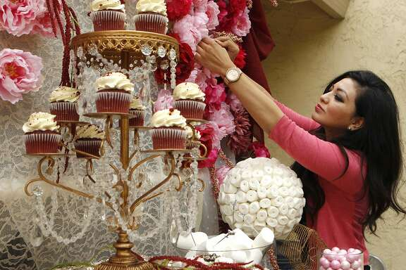 "Geraldine Orozco, founder and creative director of Bay Area Candy Buffet, arranges flowers during a ""dress rehearsal"" to prepare to cater for a client's wedding on Wednesday, pictured Tuesday, April 21, 2015, at her home in Union City, Calif. Bay Area Candy Buffet caters sweets to clients. Orozco uses Thumbtack.com, which connects consumers to home professionals."