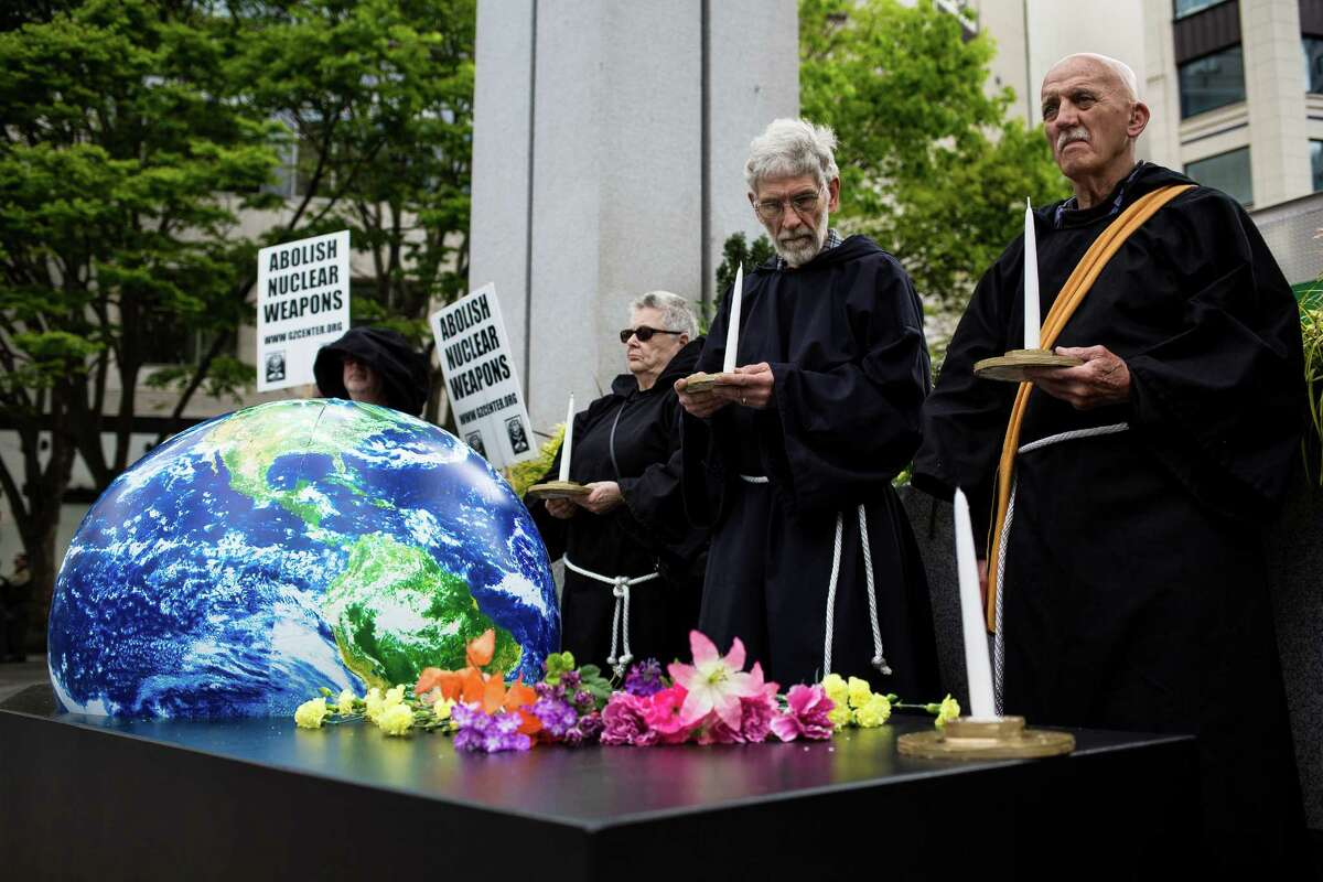 Decked out in dark robes while carrying a globe set within a wooden coffin, peace activists from the Ground Zero Center for Nonviolent Action conduct a mock funeral for the Earth in response to the increasing risk of nuclear war, photographed Tuesday, April 21, 2015, in Seattle, Washington. On the eve of Earth Day, monks carried the casket through downtown Seattle to the Henry Jackson Federal Building before visiting the offices of Senator Patty Murray and Maria Cantwell.