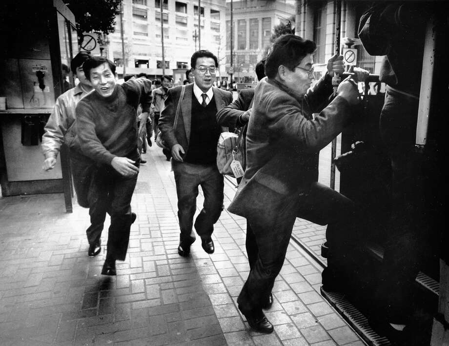 Three tourists rush to hop a cable car at the Powell Street turnaround. Jan. 12, 1988. Photo: Scott Sommerdorf, The Chronicle