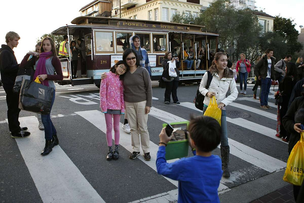 As a Hyde Street cable car passes by, tourists stand in the crosswalk taking pictures of world-famous Lombard Street in San Francisco, CA, Thursday, January 2, 2014.