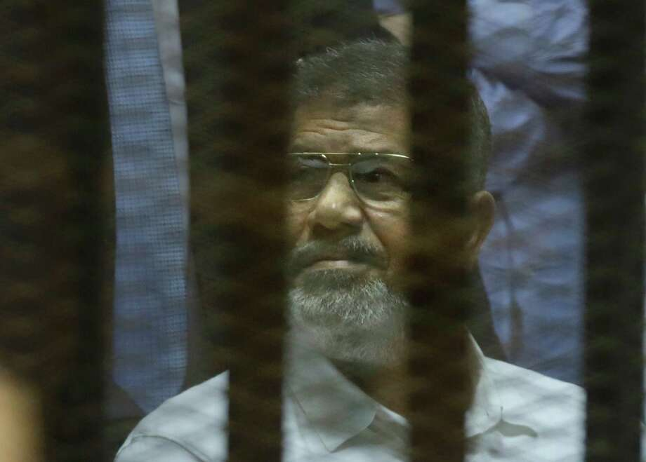 Egypt's ousted President Mohammed Morsi sits in a soundproof glass cage at his sentencing hearing Tuesday in Cairo. inside a makeshift courtroom at Egypt's national police academy in Cairo, Egypt, Tuesday, April 21, 2015. An Egyptian criminal court on Tuesday, sentenced Morsi to 20 years in prison over the killing of protesters in 2012, the first verdict to be issued against the country's first freely elected leader. (AP Photo/Amr Nabil) Photo: Amr Nabil, STF / AP