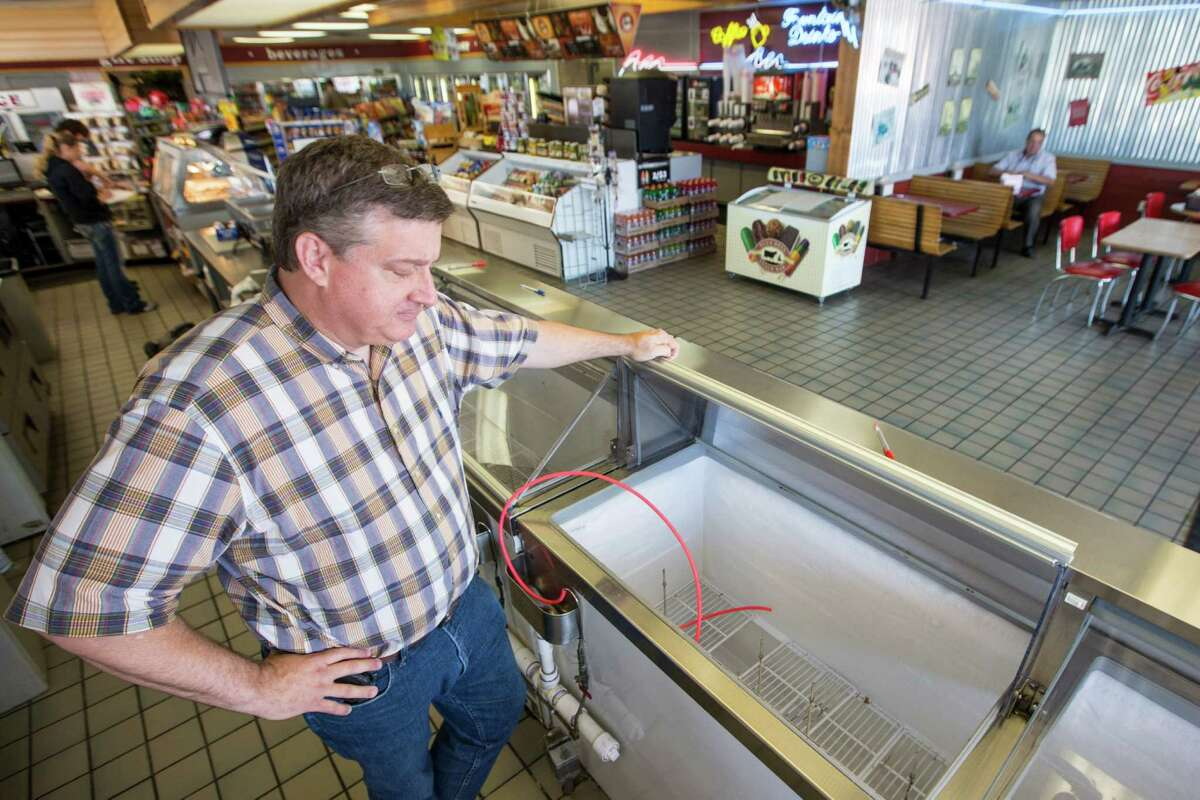 Brett Smith, owner of Scoops Ice Cream, looks over the empty ice cream case on Tuesday, April 21, 2015, in Brenham. In compliance with the Blue Bell Ice Cream recall, Smith pulled all ice cream from his freezers. ( Brett Coomer / Houston Chronicle )