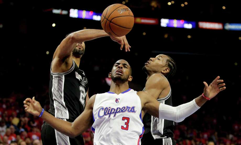 San Antonio Spurs forward Tim Duncan blocks a shot by Los Angeles Clippers guard Chris Paul as forward Kawhi Leonard tries to help during the second half of Game 1 on April 19, 2015. Photo: Chris Carlson /Associated Press / AP