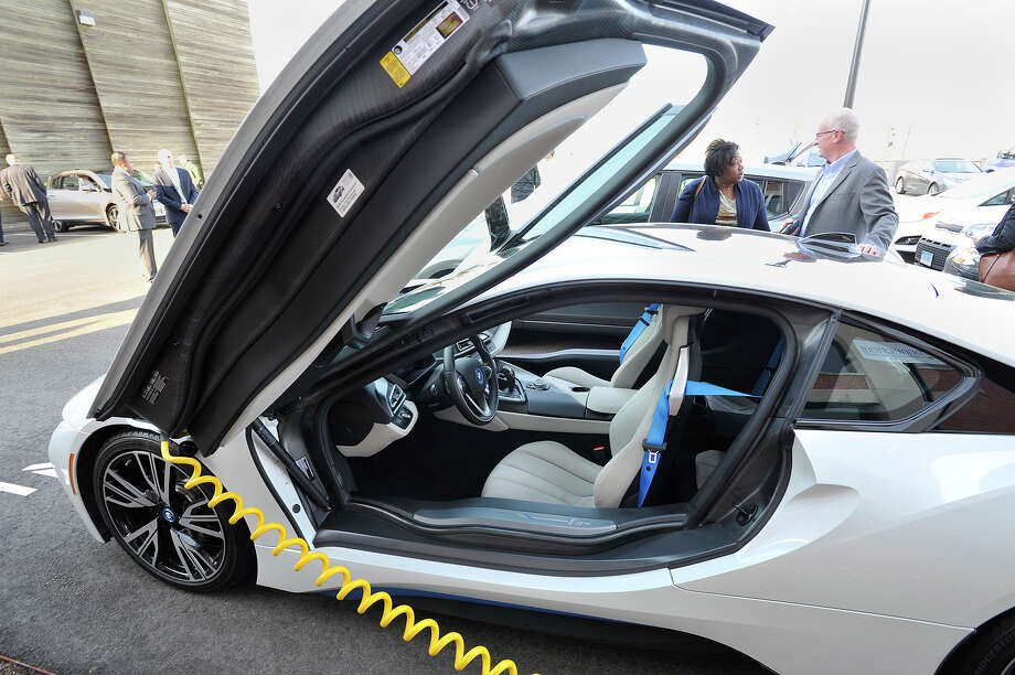 Tracey Alson and Watson Collins, both with Eversource Energy, talk while looking over a BMW i8 during the Experience Electric event held outside Sustainable America in Stamford, Conn., on Tuesday, April 21, 2015. Photo: Jason Rearick / Stamford Advocate