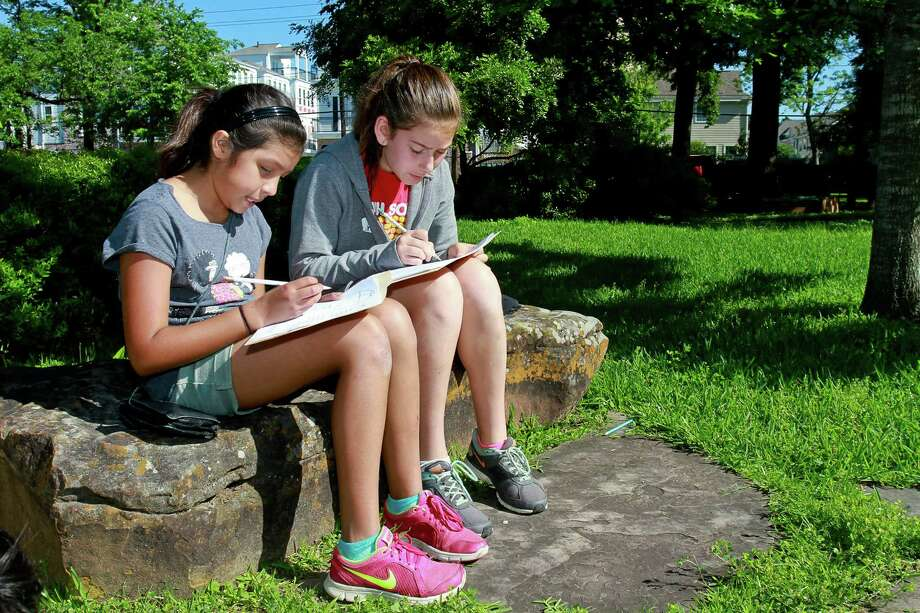 "Aurora Mindiola, left, and Lara Manega, both 11, work outdoors on a math problem as part of an ""alternative education"" event sponsored by Community Voices for Public Education.  Photo: Gary Fountain, Freelance / Copyright 2015 by Gary Fountain"