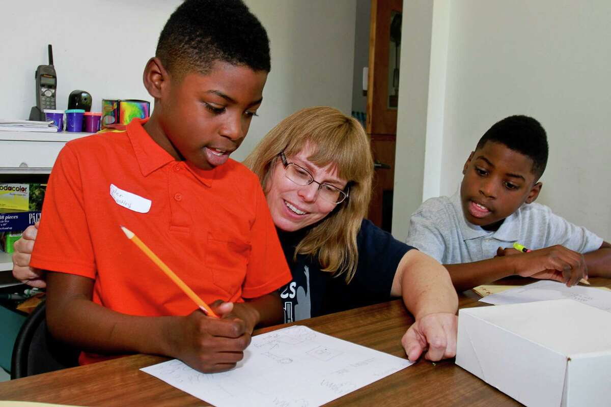 Twins Tyler, left, and Tylan Brantley, 9, work with Jamie Volkmer at the Like Oak Friends Meeting House.