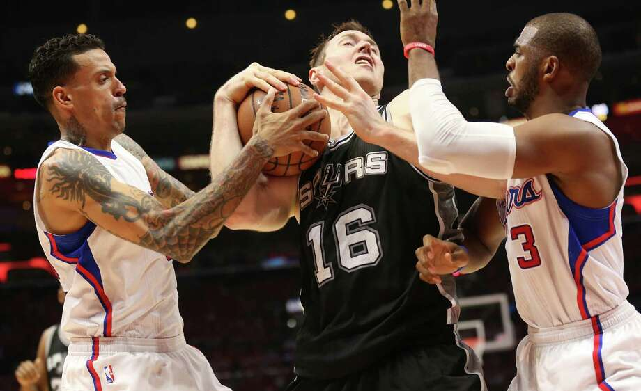 Aron Baynes of the San Antonio Spurs fights for the ball with Matt Barnes (left) and Chris Paul (right) of the Los Angeles Clippers during Game 1 of the Western Conference quarterfinals of the 2015 NBA playoffs at Staples Center on April 19, 2015 in Los Angeles, California. The Clippers won 107-92. Photo: Stephen Dunn /Getty Images / 2015 Getty Images