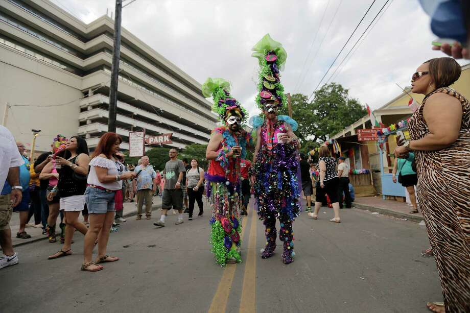 Luis Hernandez (left) and Troy Dow wear festive costumes while attending the 2015 Night In Old San Antonio at La Villita on Tuesday, Apr. 21, 2015. The smell of food and the sounds of music filled the sky as patrons make the slow crawl in search of anticuchos or chicken on a stick. Some adorned colorful headwear but many just gathered for the annual fiesta event which benefits the San Antonio Conservation Society. Photo: Kin Man Hui, San Antonio Express-News / ©2015 San Antonio Express-News