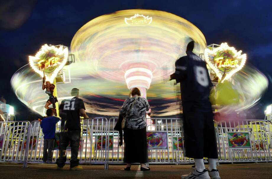 The Fighter ride spins during Fiesta's carnival at the Alamodome in San Antonio on Tuesday, April 21, 2015. Photo: Matthew Busch, For San Antonio Express-News / © Matthew Busch