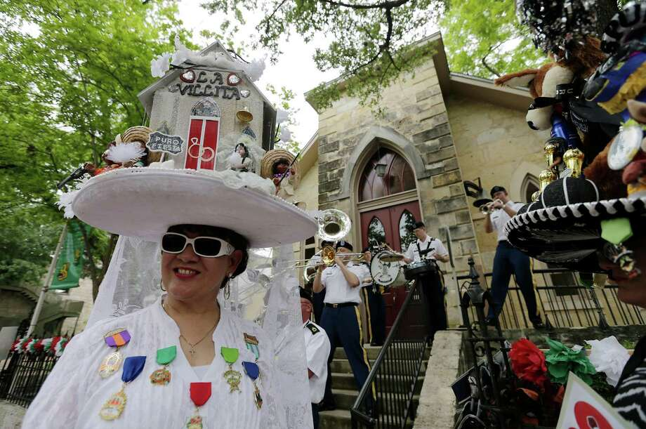 Pauline Gonzales dons a hat replica of the Little Church at La Villita in front of the church during the opening of NIOSA. Photo: Kin Man Hui /San Antonio Express-News / ©2015 San Antonio Express-News