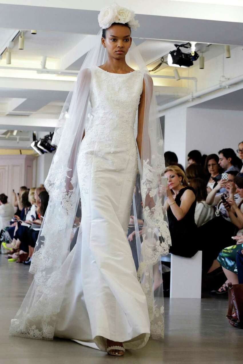 In this April 18, 2015 photo, a model wears a creation from the Oscar de la Renta Bridal Spring 2016 collection in New York. Peter Copping, hired last October as artistic director of the luxury label, retained much of the classic de la Renta glamour but added a few more modern-looking silhouettes, some new takes on fabric work, and some silvery sequins.