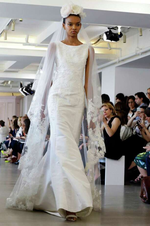 In this April 18, 2015 photo, a model wears a creation from the Oscar de la Renta Bridal Spring 2016 collection in New York. Peter Copping,  hired last October as artistic director of the luxury label, retained much of the classic de la Renta glamour but added a few more modern-looking silhouettes, some new takes on fabric work, and some silvery sequins.  Photo: Mary Altaffer, Associated Press / AP
