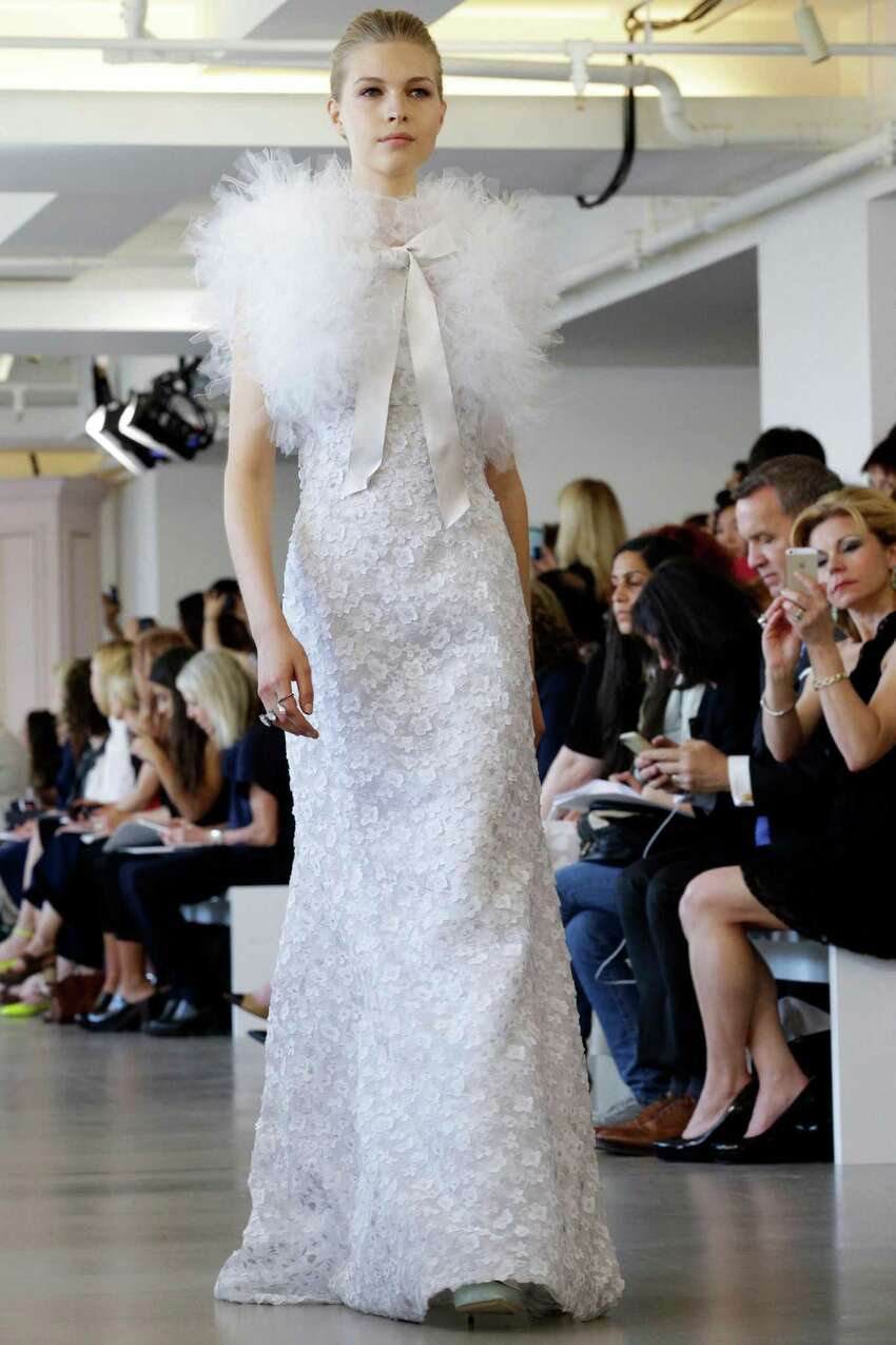 In this April 18, 2015 photo, a model wears a creation from the Oscar de la Renta Bridal Spring 2016 collection in New York. Peter Copping, hired last October as artistic director of the luxury label, retained much of the classic de la Renta glamour but added a few more modern-looking silhouettes, some new takes on fabric work, and some silvery sequins. (AP Photo/Mary Altaffer)