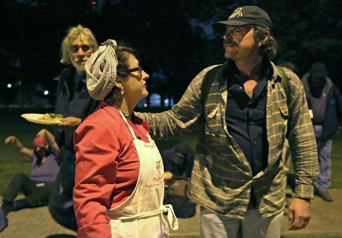 Cliff Snipes, right, homeless in San Antonio for two year, shows his gratitude to Joan Cheever, for feeding him at Maverick Park. Two weeks ago Cheever was ticketed for serving meals without the proper permit. Tuesday, April 21, 2015.