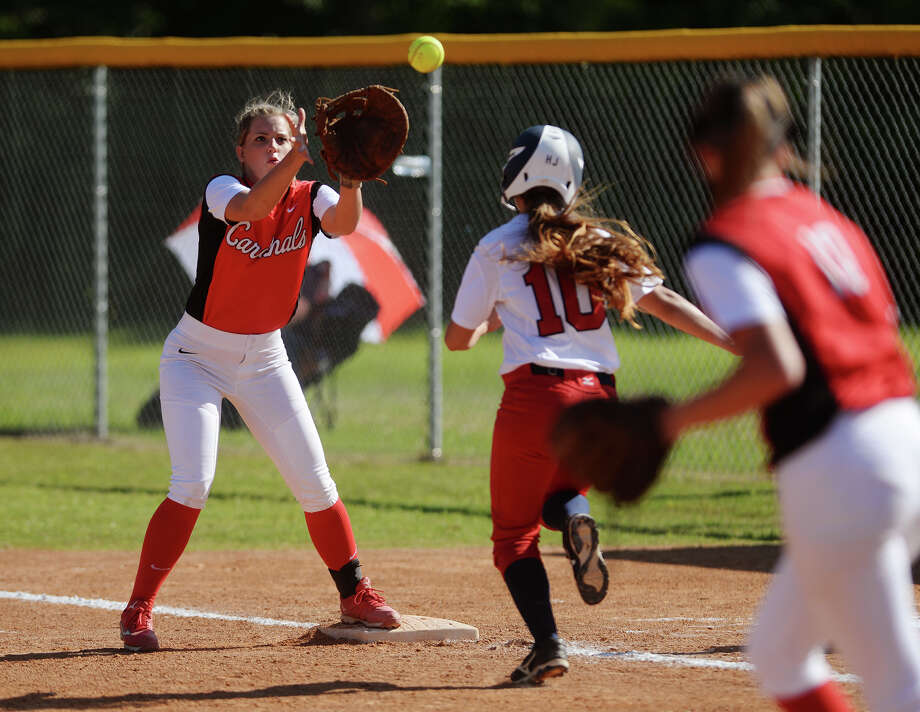 Bridge City's Skylar Kahla, No. 5, reaches out for a catch at first as Hardin-Jefferson's Karly Smith, No. 10, heads for the base Tuesday. The Hardin-Jefferson Lady Hawks hosted the Bridge City Cardinals for the District 24-4A showdown Tuesday afternoon.  Photo taken Tuesday 4/21/15  Jake Daniels/The Enterprise Photo: Jake Daniels / ©2015 The Beaumont Enterprise/Jake Daniels