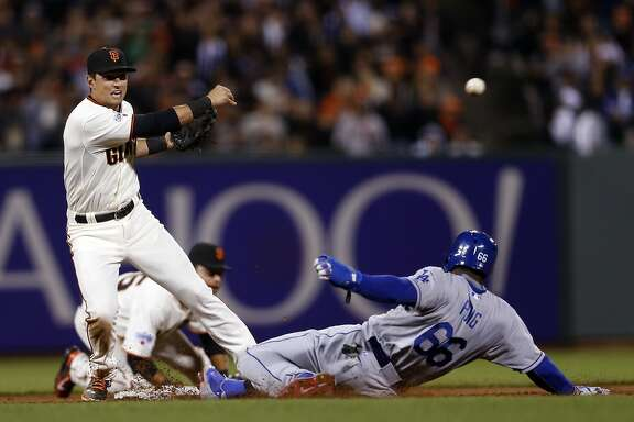 San Francisco Giants' Joe Panik relays to first base after forcing out Los Angeles Dodgers' Yasiel Puig to start inning ending double play in 6th inning during MLB game at AT&T Park in San Francisco, Calif., on Tuesday, April 21, 2015.