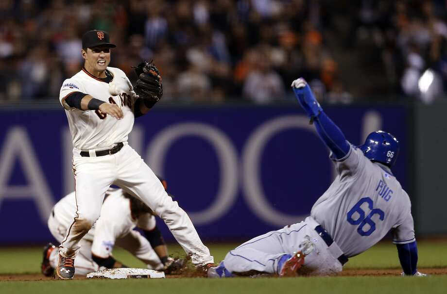 San Francisco Giants' Joe Panik relays to first base after forcing out Los Angeles Dodgers' Yasiel Puig at AT&T Park on Tuesday, April 21, 2015. Photo: Scott Strazzante, The Chronicle