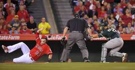 CORRECTS CITY TO ANAHEIM, INSTEAD OF LOS ANGELES - Los Angeles Angels' C.J. Cron, left, looks to home plate umpire Marty Foster, center, for the call after sliding in safely at home under the tag of Oakland Athletics catcher Josh Phegley on a single by Johnny Giavotella during the sixth inning of a baseball game, Tuesday, April 21, 2015, in Anaheim, Calif. (AP Photo/Mark J. Terrill)