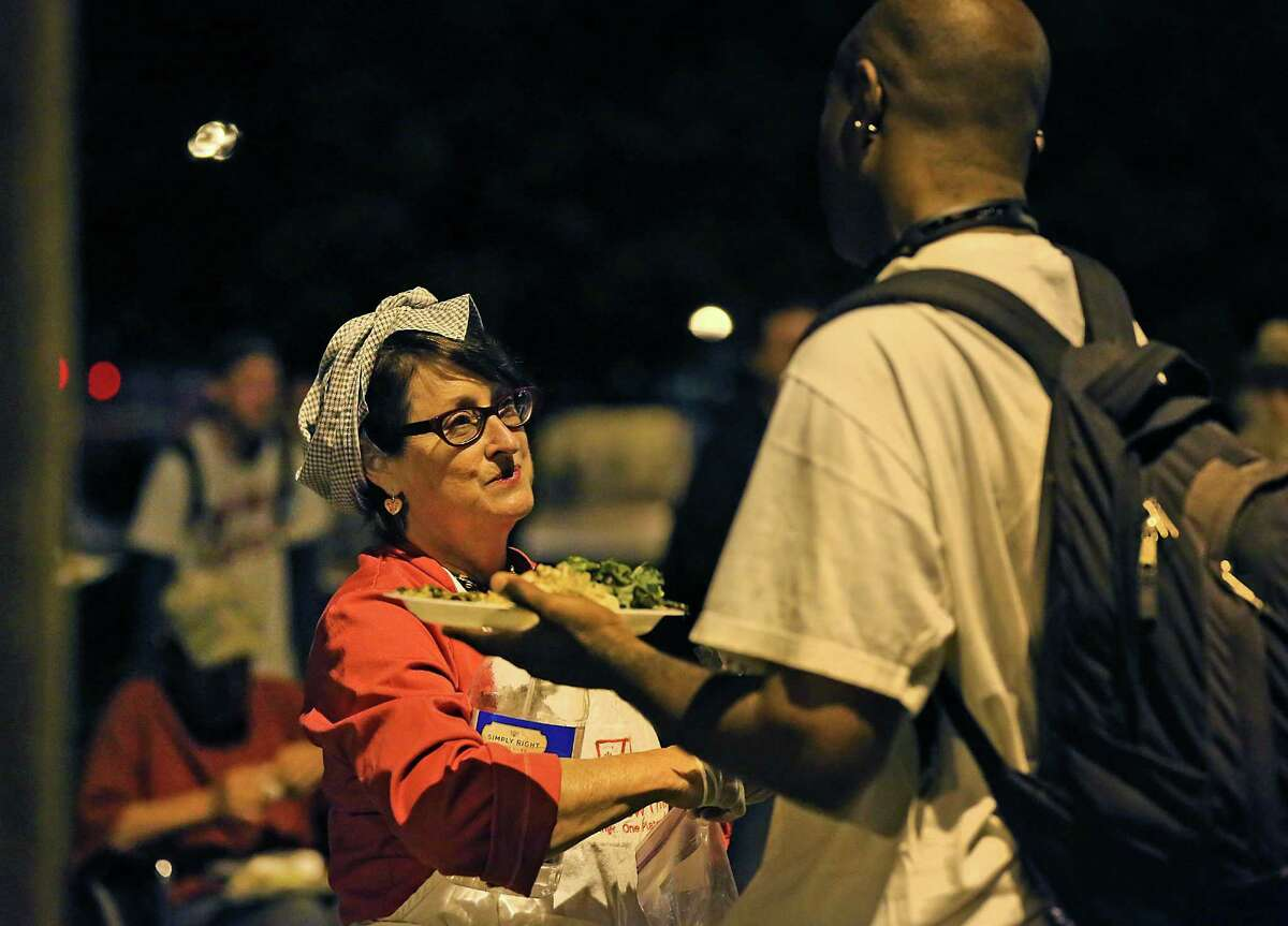 Joan Cheever, left, talks with Shaundale Whitmore after he received his plate from Cheever's food truck at Maverick Park where she fed close to 40 people who live on the streets. Tuesday, April 21, 2015.