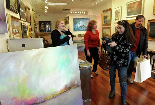 Asher Weiner, right, and his wife Nirit Weiner of Voorheesville purchase art from the Sorelle Gallery, owned by Sandra Pelletier, center, gallery assistant director Heather Pominville,left, during small business Saturday at Stuyvesant Plaza on Saturday Nov. 30, 2013 in Albany, N.Y. (Michael P. Farrell/Times Union) Photo: Michael P. Farrell, /518Life / 00024847A