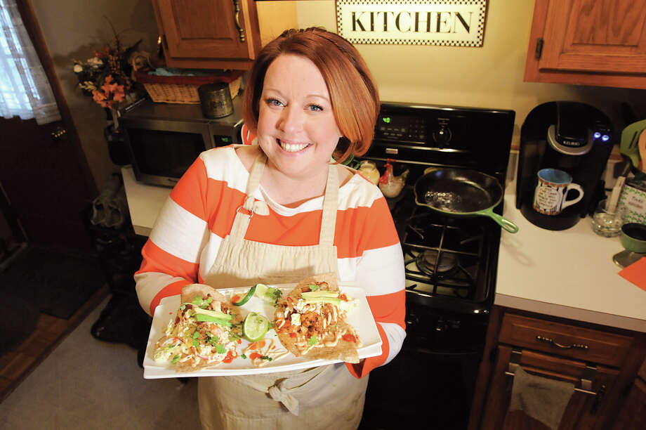 Jill Kavanagh holds her spicy sriracha shrimp tacos with mango slaw and fresh avocado on Tuesday, March 3, 2015, at her home in Troy, N.Y. Photo: CINDY SCHULTZ/ALBANY TIMES UNION / 00030756A