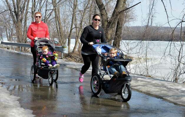 Florence Steinberg, left, and 16-month-old Vivian Steinberg and Jennifer Tychostup with 20-month-old Braden Tychostup, all of Watervliet, jog/stroll along the Hudson River on the Mohawk-Hudson Bike-Hike trail Tuesday March 11, 2014, in Watervliet, NY.  (John Carl D'Annibale / Times Union) Photo: /Times Union