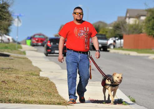 Juan Alonzo-Miranda walks with his service dog, Goldie, near their far West Side home. Photo: Robin Jerstad /San Antonio Express-News