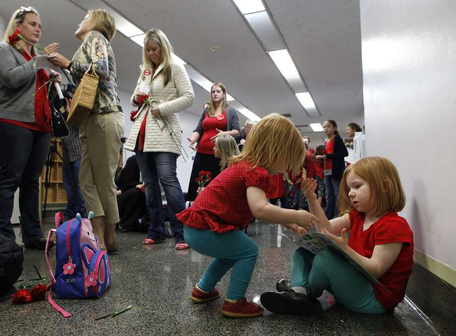 Alexis Frederickson (right), age 4, and her two-year-old sister Camilla wait with their mother Kirstin to hear the Senate Education Committee's decision on SB277 at the California State Capitol, Wednesday, April 22, 2015, in Sacramento, Calif. Kirstin, from Livermore, is against the bill. The bill was approved with a 7-2 vote and now goes to the Senate Judiciary Committee. SB277 would eliminate the personal-belief exemption, the option California parents use to skip their childÕs school immunizations, but still allow children to be exempt for medical reasons. Photo: Santiago Mejia, The Chronicle