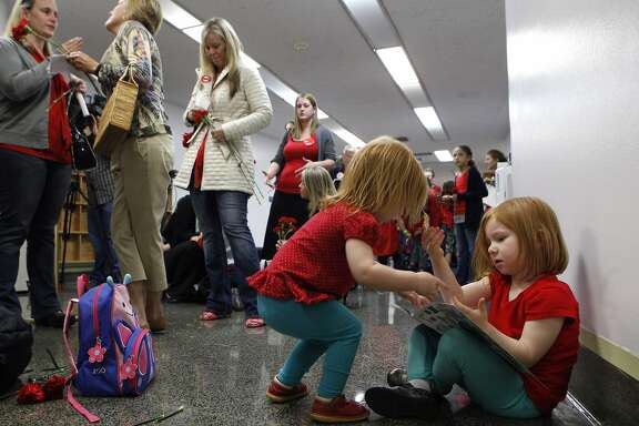 Alexis Frederickson (right), age 4, and her two-year-old sister Camilla wait with their mother Kirstin to hear the Senate Education Committee's decision on SB277 at the California State Capitol, Wednesday, April 22, 2015, in Sacramento, Calif. Kirstin, from Livermore, is against the bill. The bill was approved with a 7-2 vote and now goes to the Senate Judiciary Committee. SB277 would eliminate the personal-belief exemption, the option California parents use to skip their childÕs school immunizations, but still allow children to be exempt for medical reasons.